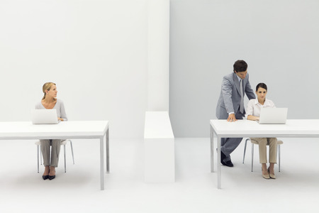 Two women working in office, man standing behind one with his hand on her shoulder