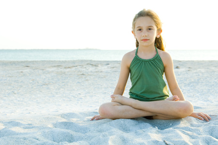 over the edge: Girl sitting cross-legged on beach, full length LANG_EVOIMAGES