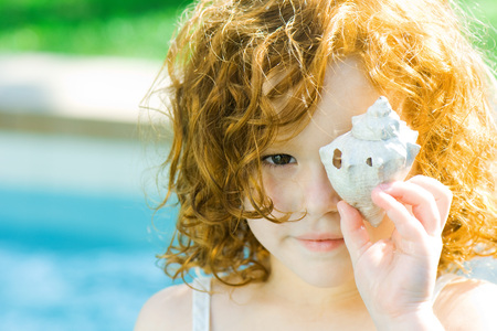 Little girl holding seashell in front of face, looking at camera