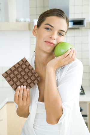 Woman holding large chocolate bar in one hand, apple in the other, smiling at camera