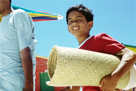 Boy carrying rolled up beach mat, smiling at camera LANG_EVOIMAGES