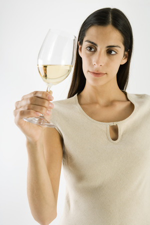 Woman looking at white wine in glass, close-up LANG_EVOIMAGES
