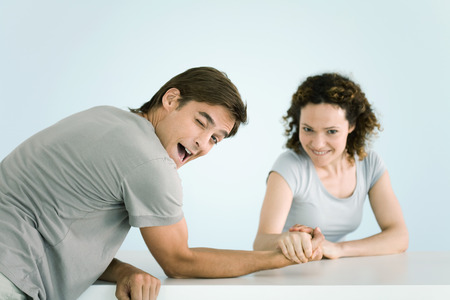 Couple arm wrestling, both looking at camera, man winking as he lets woman win