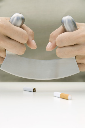 Person cutting cigarette in half with meat cleaver, cropped view of hands LANG_EVOIMAGES