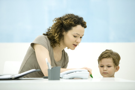 Young mother sitting at desk, interacting with little boy