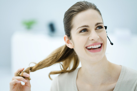 Young woman twirling her hair, wearing headset and looking away, smiling