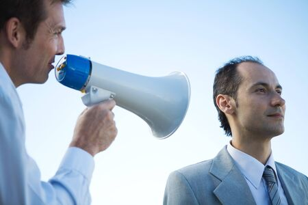 Businessman standing beside colleague, shouting into megaphone LANG_EVOIMAGES