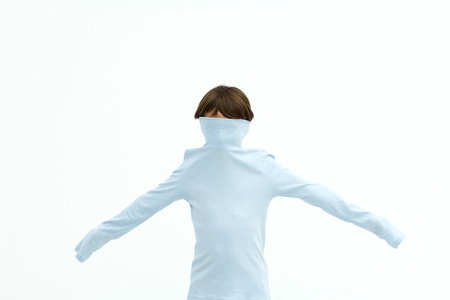 introversion: Boy wearing turtleneck pulled over his face, arms outstretched LANG_EVOIMAGES