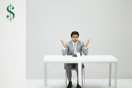 Man sitting at desk with adding machine, puffed cheeks, hands raised