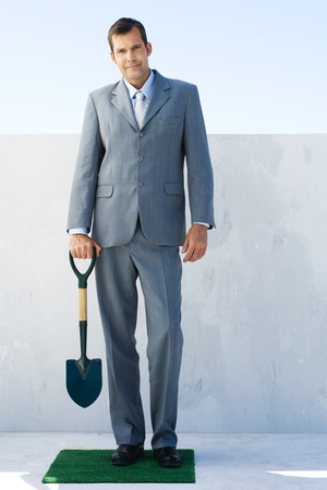 Man in suit, standing on small patch of artificial turf, holding shovel, looking at camera