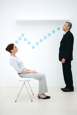 postit note: Man and woman face to face with adhesive notes forming a path between them, looking away, side view LANG_EVOIMAGES