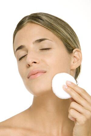 Woman using powder puff on cheek, eyes closed