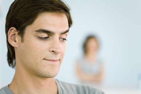 Man making sideways glance over shoulder, woman with arms folded in background LANG_EVOIMAGES