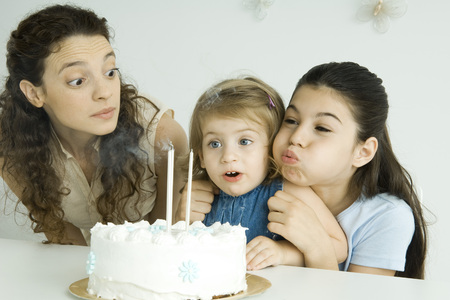 Girl helping younger sister blow out candles on birthday cake, mother watching