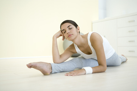 Woman doing split, holding head, eyes closed LANG_EVOIMAGES