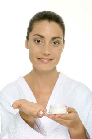 Woman in bathrobe holding moisturizer on hand, smiling at camera