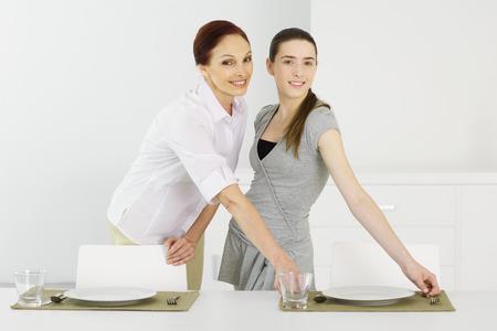 estereotipo: Madre e hija adolescente poniendo la mesa juntos, sonriendo a la cámara