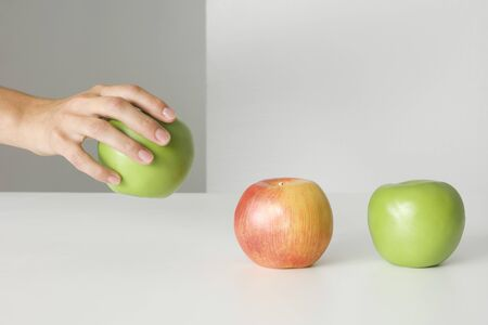 Hand picking up an apple, two other apples sitting in a row, cropped view LANG_EVOIMAGES