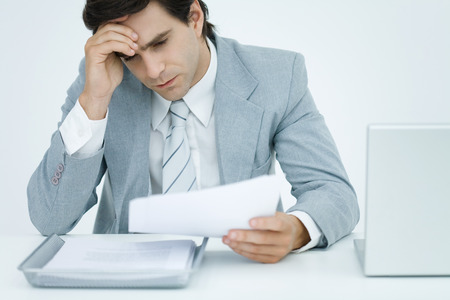 Young businessman sitting at desk, holding head and looking down at document