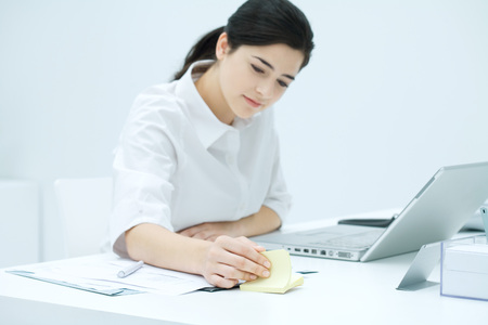 Young woman sitting at desk, flipping through adhesive note block