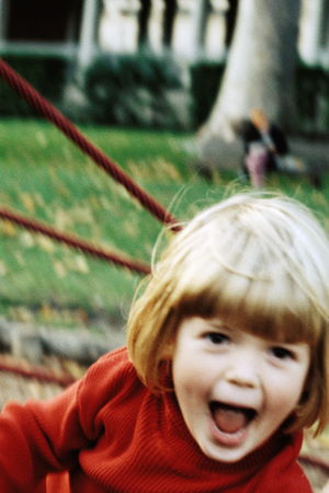 Girl on playground, making face at camera