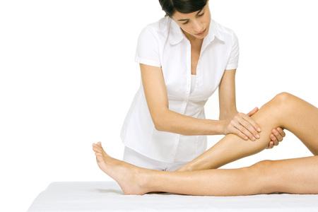 holistic view: Woman performing leg massage