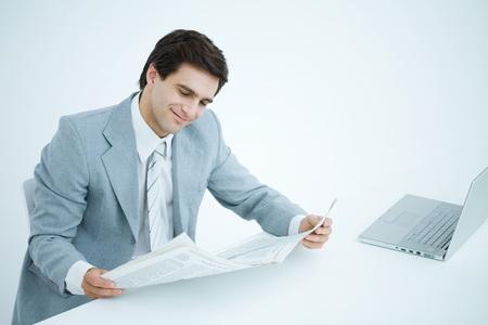 Businessman sitting at desk, reading newspaper LANG_EVOIMAGES