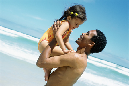 southern european descent: Man holding up daughter on beach, side view LANG_EVOIMAGES