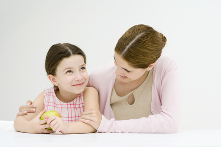 Woman sitting at table with arm around daughters shoulder, smiling, girl holding apple