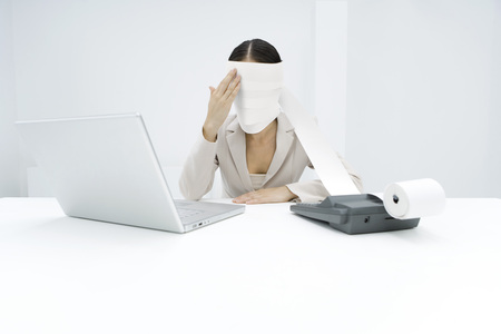 Woman sitting behind adding machine, roll paper wrapped around her head