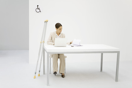 Professional woman working in office, crutches leaning against desk beside her
