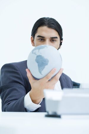 greased: Young businessman holding globe and looking down at it