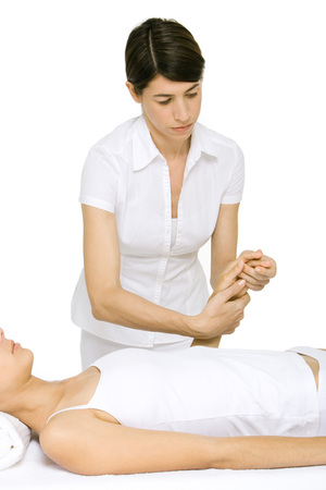 holistic view: Massage therapist massaging womans hand
