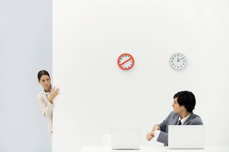 Woman peeking around corner as boss points at wristwatch, clocks on wall in background