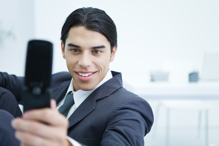 Young businessman using cell phone to take picture of himself, smiling