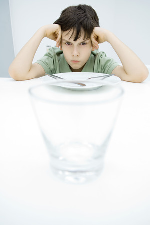 Boy sulking at kitchen table, leaning on elbows, empty glass in foreground LANG_EVOIMAGES