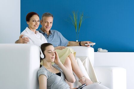 Family together in living room, parents smiling at camera, teen girl listening to headphones