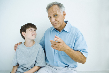 Man sitting with arm around grandsons shoulders, man looking at camera LANG_EVOIMAGES
