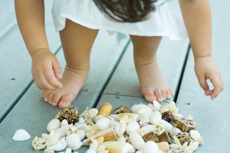 Child bending over pile of seashells, cropped view of low section