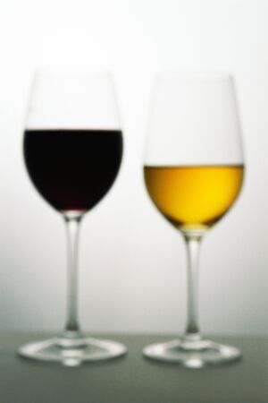 Two wine glasses with red and white wines, defocused