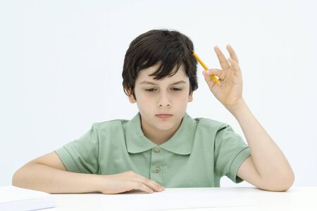 distractions: Boy sitting at table, holding pencil against head, looking down