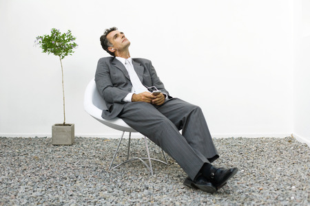 dry suit: Businessman relaxing in rock garden, listening to mp3 player LANG_EVOIMAGES