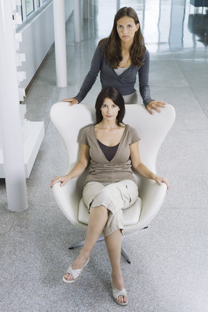 authoritative woman: Woman sitting in chair, teen daughter standing behind her, both looking up at camera