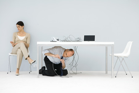 Man kneeling under desk, connecting tangled wires, woman sitting in chair, looking at hand