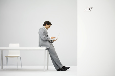 Businessman leaning against desk, using laptop computer, cursor graphic in foreground