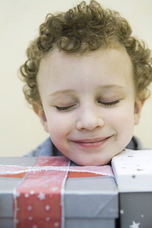 Child resting head on gift wrapped boxes, eyes closed and smiling