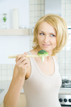 Blonde woman holding piece of broccoli with chopsticks LANG_EVOIMAGES