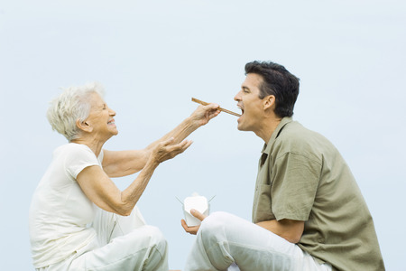 Senior woman feeding adult son with chopsticks, laughing, side view