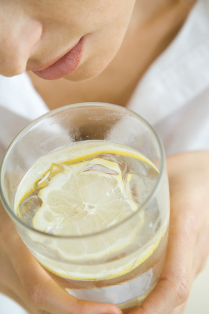 Woman holding glass of water with floating lemon slice, close-up, cropped LANG_EVOIMAGES