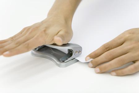 Hands using hole puncher LANG_EVOIMAGES